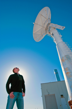 Brian Post stands under an antenna at the ground station at Sandia National Labs during the MTI satellite's 55,000th orbit (photo by Randy Montoya).