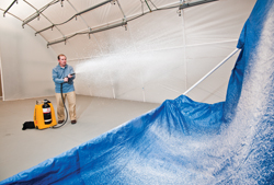 Researcher Mark Tucker demonstrates application of Sandia-developed decontamination foam.