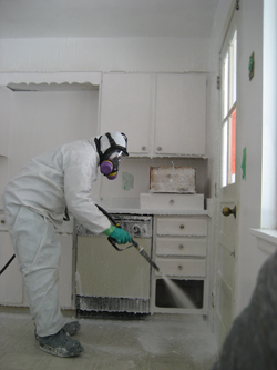 A remediator sprays Crystal Clean on surfaces of a house contaminated with methamphetamine.