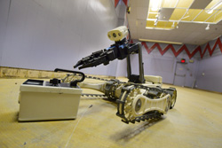 Robot picks up radiation detector during 2015 Robot Rodeo