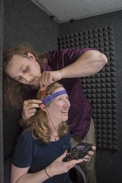 Mike Trumbo adjusts an electrode on Laura Matzen's head