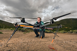 Dave Novick examines an octocopter against a background of grey clouds