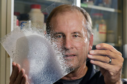 Sandia engineer Mark Tucker with a foam-covered plastic pane.