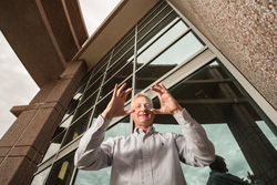 Materials physicist Paul Clem holds a sample of nanoparticle coated glass in front of an office building.