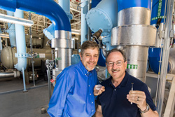 Curtis Mowry and Mike Siegal with tiny nanoporous carbon coated SAW sensors in front of blue water pipes