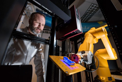 Brad Boyce watches a yellow commercial robot scan a 3D-printed test part with blue light.