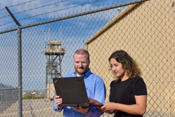 Alex Dessanti and Karina Munoz-Ramos with laptop in front of fence and guard tower