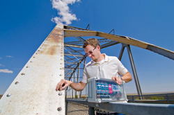 Man positions small, clear sensor on an old rusty bridge. Blue sky in background. In his other hand is a complex control system.