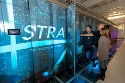 Sandia engineer and Westwind owners looking at Astra supercomputer.