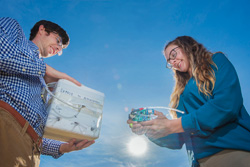 Danny Bowman holding a stryofoam box (left) Sarah Albert holding an infrasound sensor (right) with a bright blue sky as background