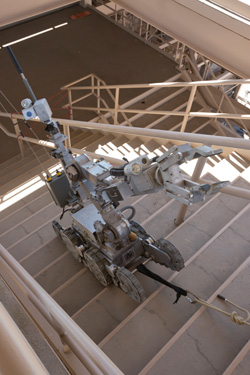 Robot on treads climbing a flight of concrete stairs with a black safety line.