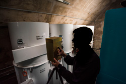 A man in profile scans three white canisters with a brass box -- the new neutron detection equipment