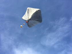 Greyish balloon with 5 sides and several white boxes dangling below against a clear blue sky.