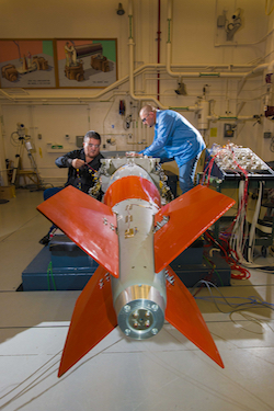 Photograph of Sandia technologists Curt Tenorio and Jessie Fowler install instrumentation on a B61-12 test unit for a vibration and shaker-shock test.