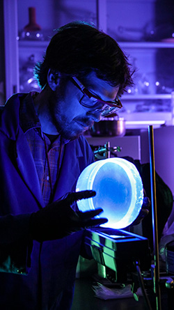 Nick Myllenbeck, a materials scientist at Sandia National Laboratories, examines glowing plastic used to detect radioactive material. (Photo by Lloyd Wilson) Click on the thumbnail for a high-resolution image.