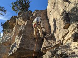 A man in outdoor gear and a mask, climbing a rock face.