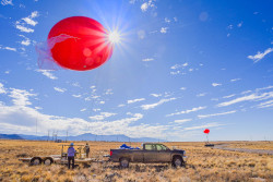 Foreground: Two people behind a truck below a large red balloon. Background: another truck and red balloon.