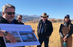 Mark Rigali, front, with poster and three on-lookers with Colorado mountains in the background.