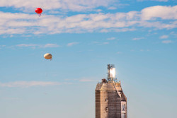 Two small balloons against a blue sky to the left of a large tower with a