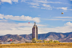 Three balloons, a 200 foot tall tower, the Sandia mountains, and a field of mirrors.