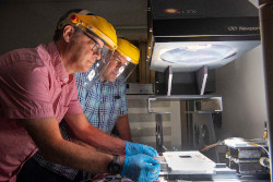 Two men in protective helmats look at a solar module under a bright light.