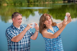 Two scientists look at hand-sized white membranes, water and lush trees in background.