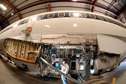 Sandian Kevin Howard inspects electrical wiring in the wheel well of a retired Boeing 727 at Sandia's FAA Airworthiness Assurance NDI Validation Center.  The wing on the 727 has been removed.