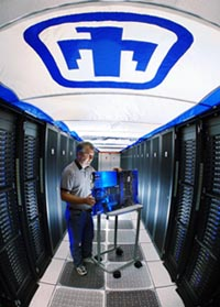 John Zepper inspects a Thunderbird supercomputer component under the Sandia Thunderbird insignia.