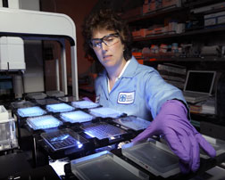 Biochemist Joanne Volponi prepares samples of cellulase enzymes for activity assaying in a high-throughput, fluid-handling robotic system.